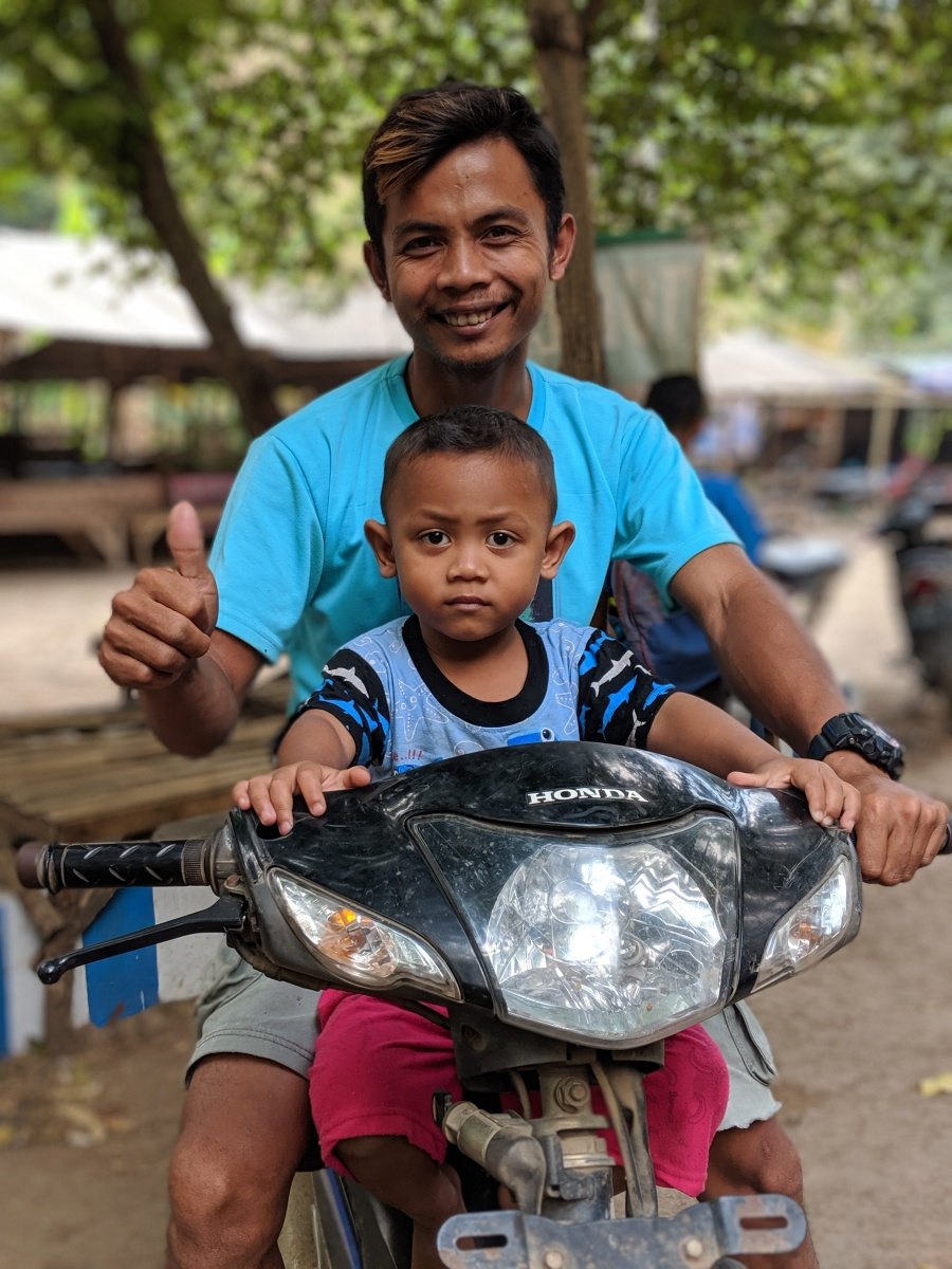 A man and his son on a scooter in Indonesia